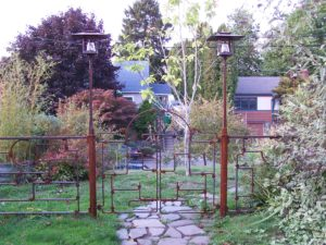 Craftsman inspired forged steel gate with fence and lanterns. Private residence.